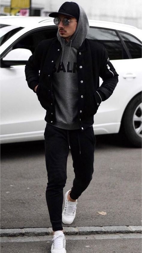 boy wearing a varsity jacket over a hoodie and jogger pants.