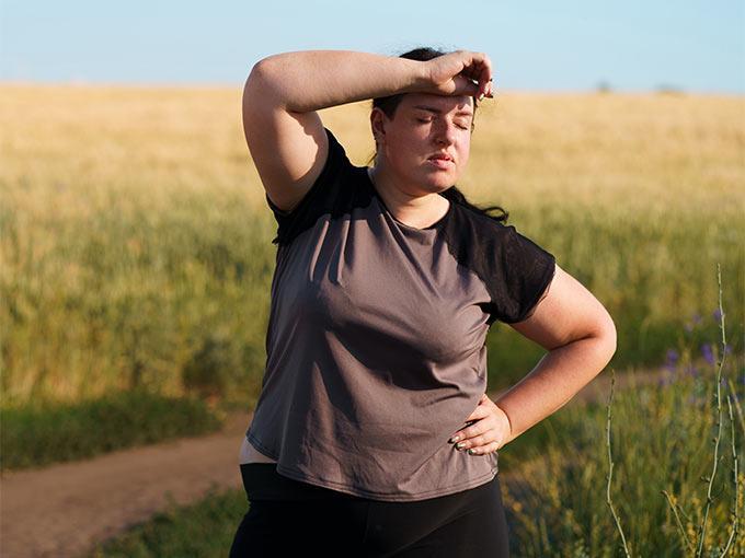 Eine Frau steht im Freien auf einem Feld und sieht angestrengt aus: Der vermehrte Hang zu schwitzen kann nicht nur durch Hitze oder Anstrengung, sondern auch durch Diabetes bedingt sein.