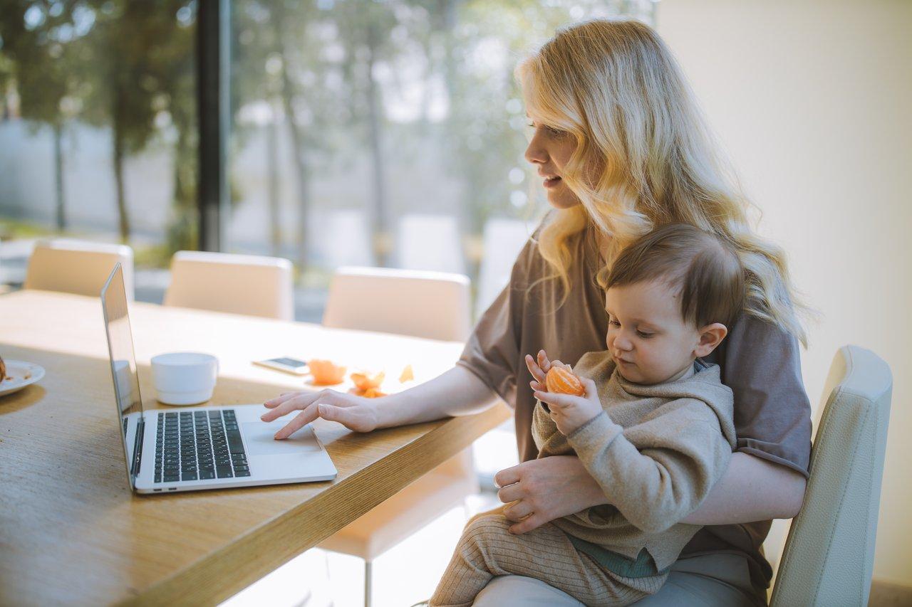 Uma mulher com um bebê no colo mexendo n0o notebook.