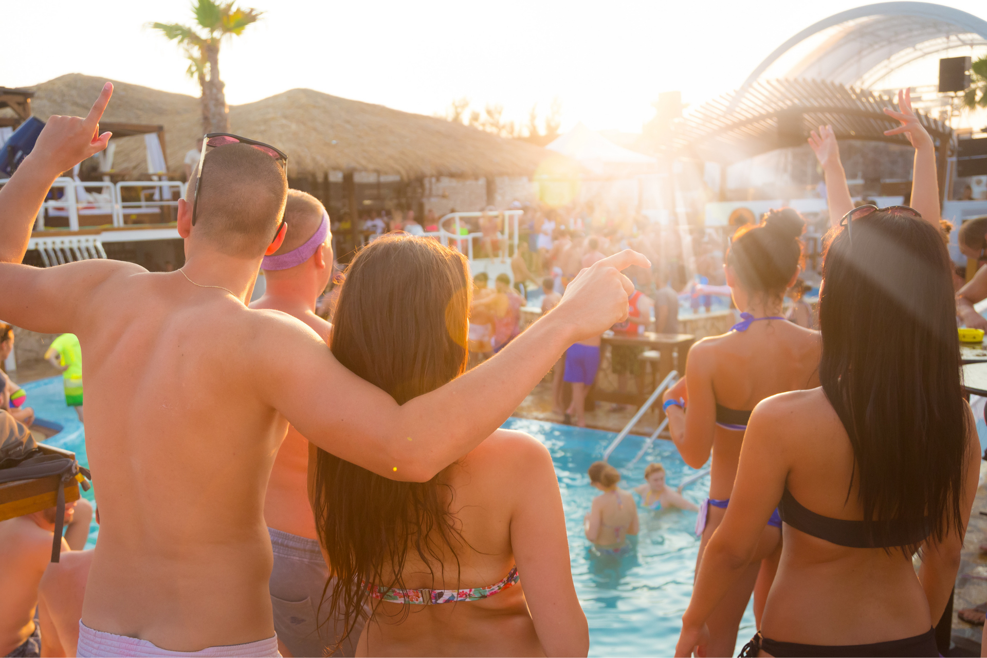 A group of people partying around a pool