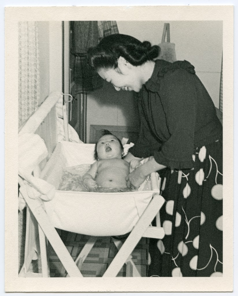 A woman bathing a baby in a barrack room at Heart Mountain.