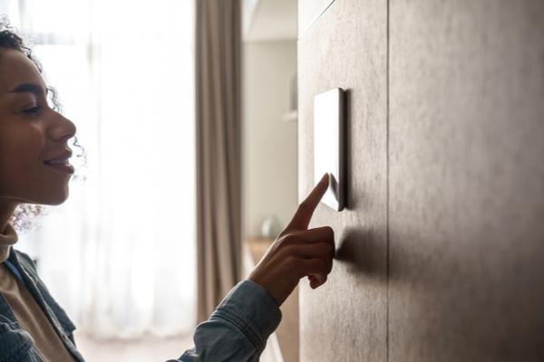 homeowner adjusting thermostat