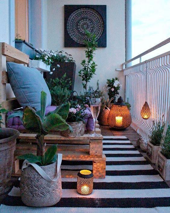 Varanda bem decorada com sofá de pallet,, muitas plantas espalhadas pelo chão, tapete listrado preto e branco, vasos com velas e quadros decorativos.