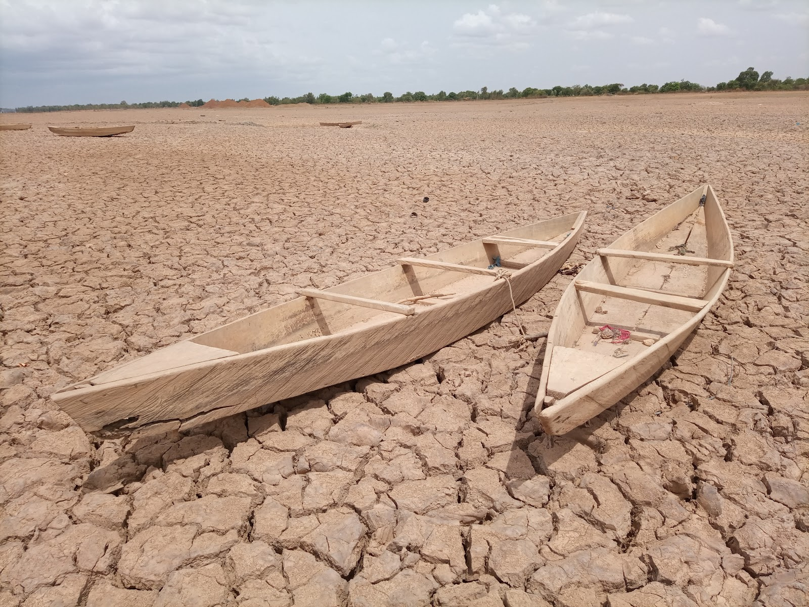 Two abandoned boats on a dried up lake.