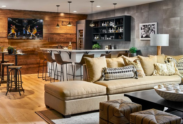 contemporary basement bar with wood accent wall, couch, corner l shaped bar, and  recessed and pendant lighting
