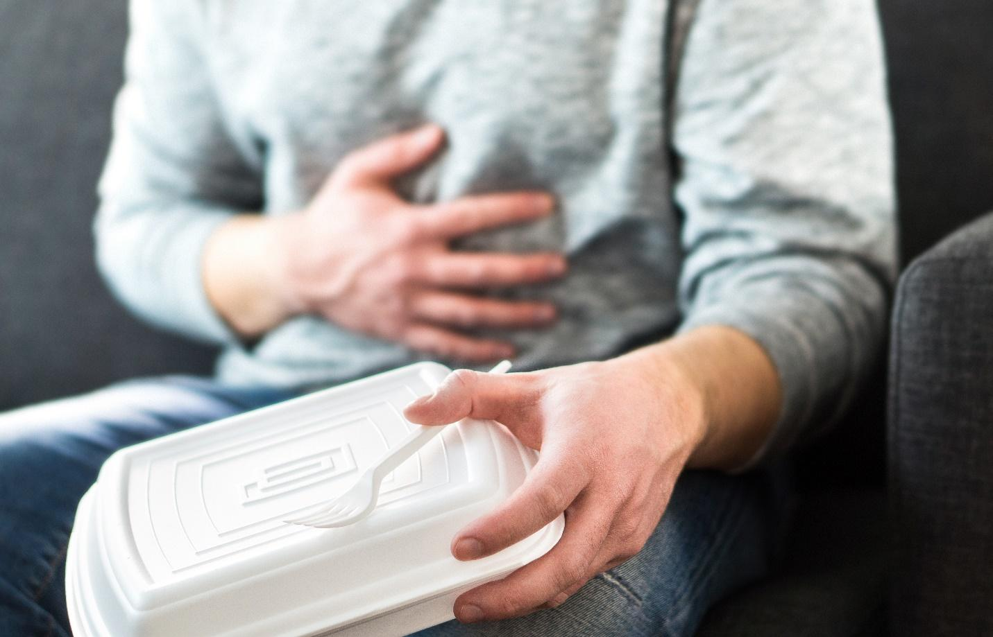man with stomachache after bad takeout food