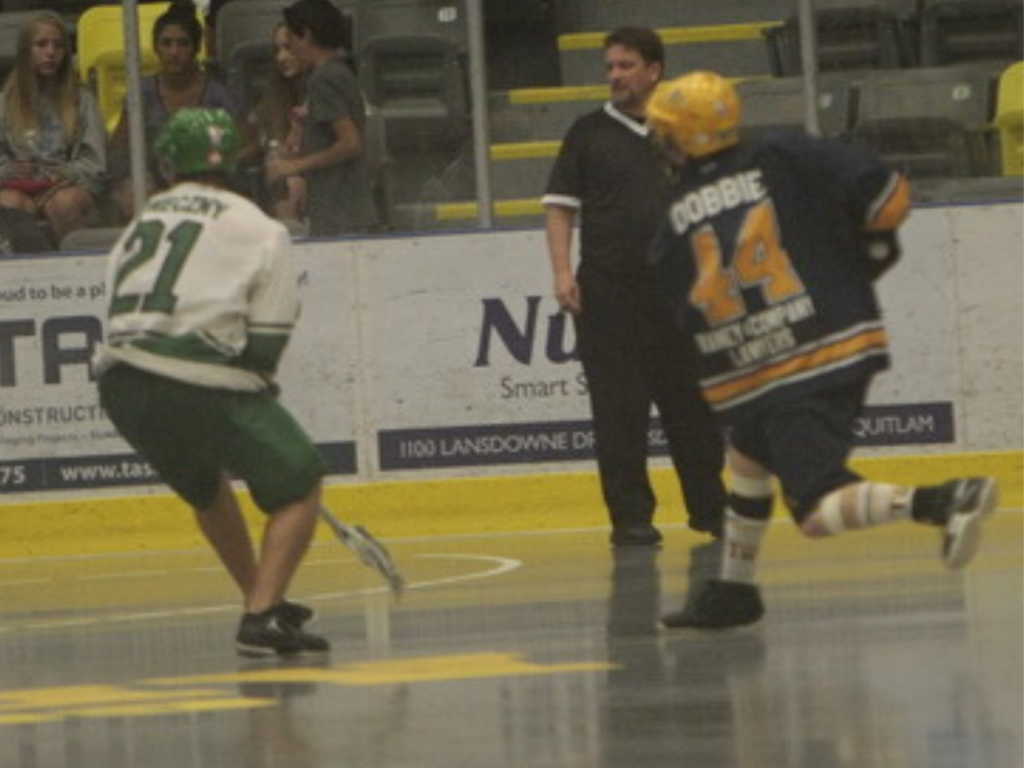 Senior A lacrosse player settinf up for a shot on net, while defender rushes to interfere