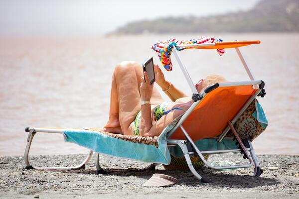 foto de uma mulher na praia lendo um kindle