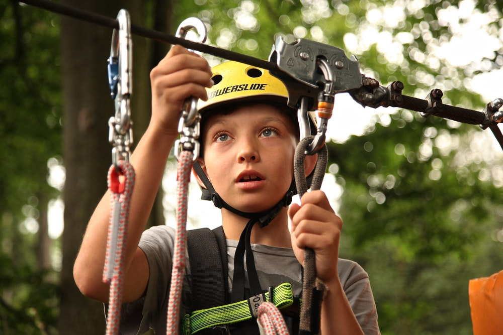 boy zip-lining with ropes and carabiners