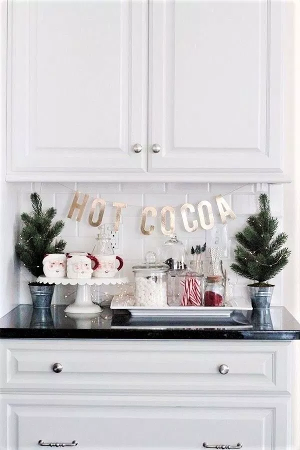 bright white kitchen with mini christmas hot cocoa station featuring mini christmas trees, santa mugs, decorative white trays and a hot cocoa sign