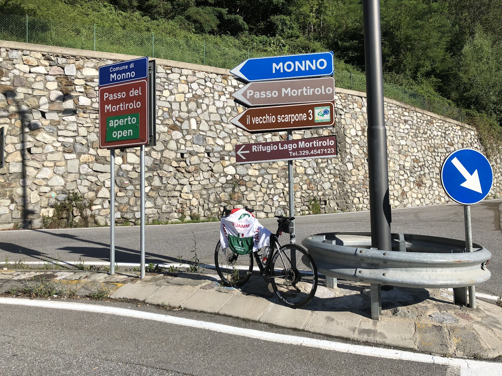 Climbing Passo del Mortirolo from Edolo - roadway sign with bike leaning against it.