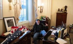 A Trump supporter identified as Richard Barnett sits inside the House speaker's office on Wednesday.