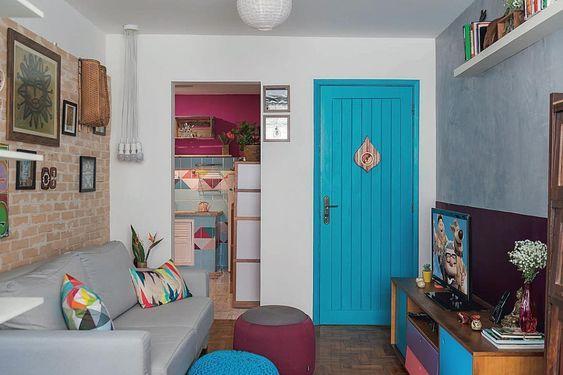 Sala rústica colorida, com porta azul, sofá cinza, poltronas coloridas, tijolinhos na parede e objetos decorativos coloridos.
