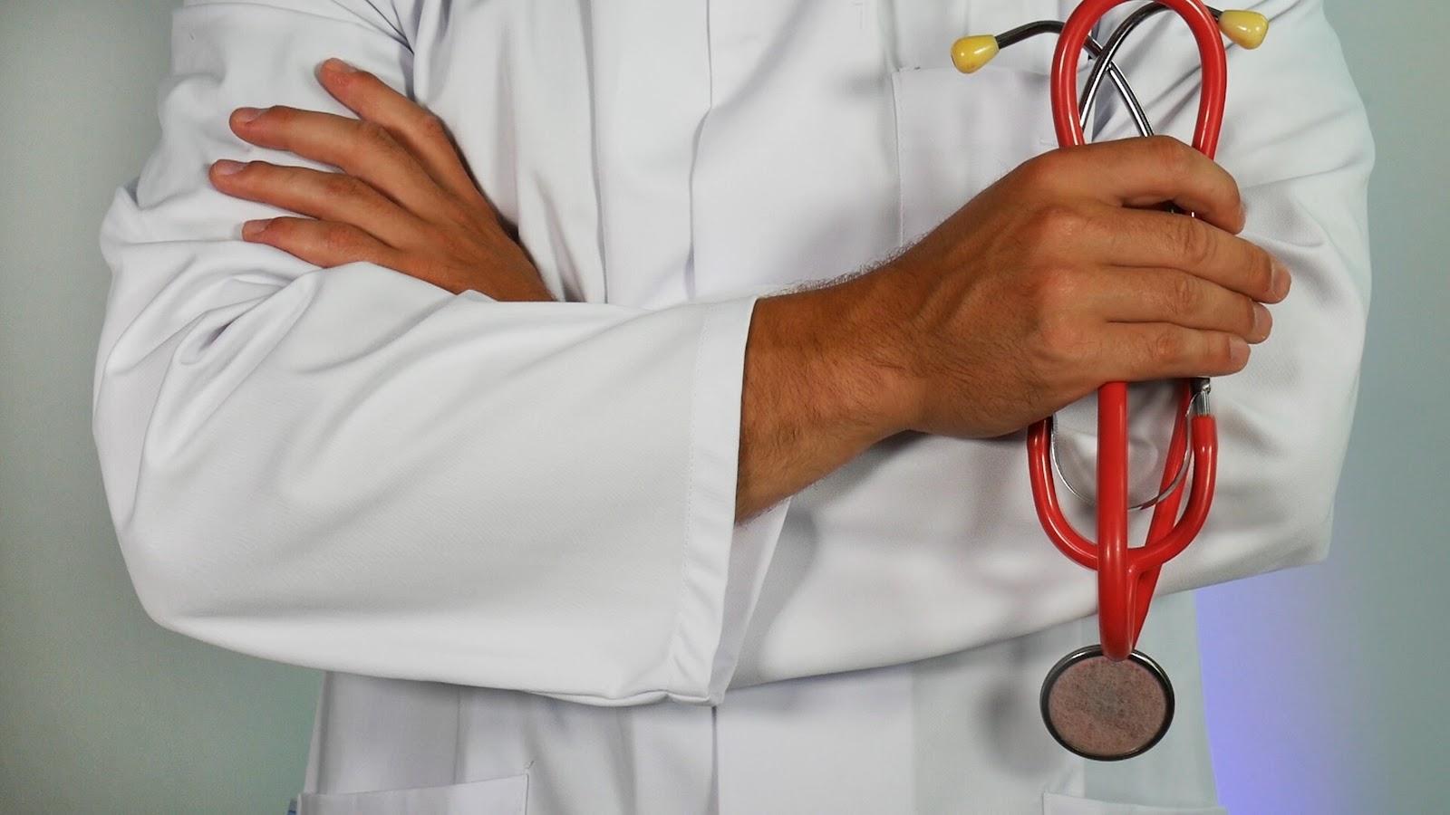 Um médico segurando seus equipamentos de trabalho.