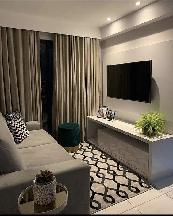 Sala com sofá cinza, rack branca, plantas e cortina longa.