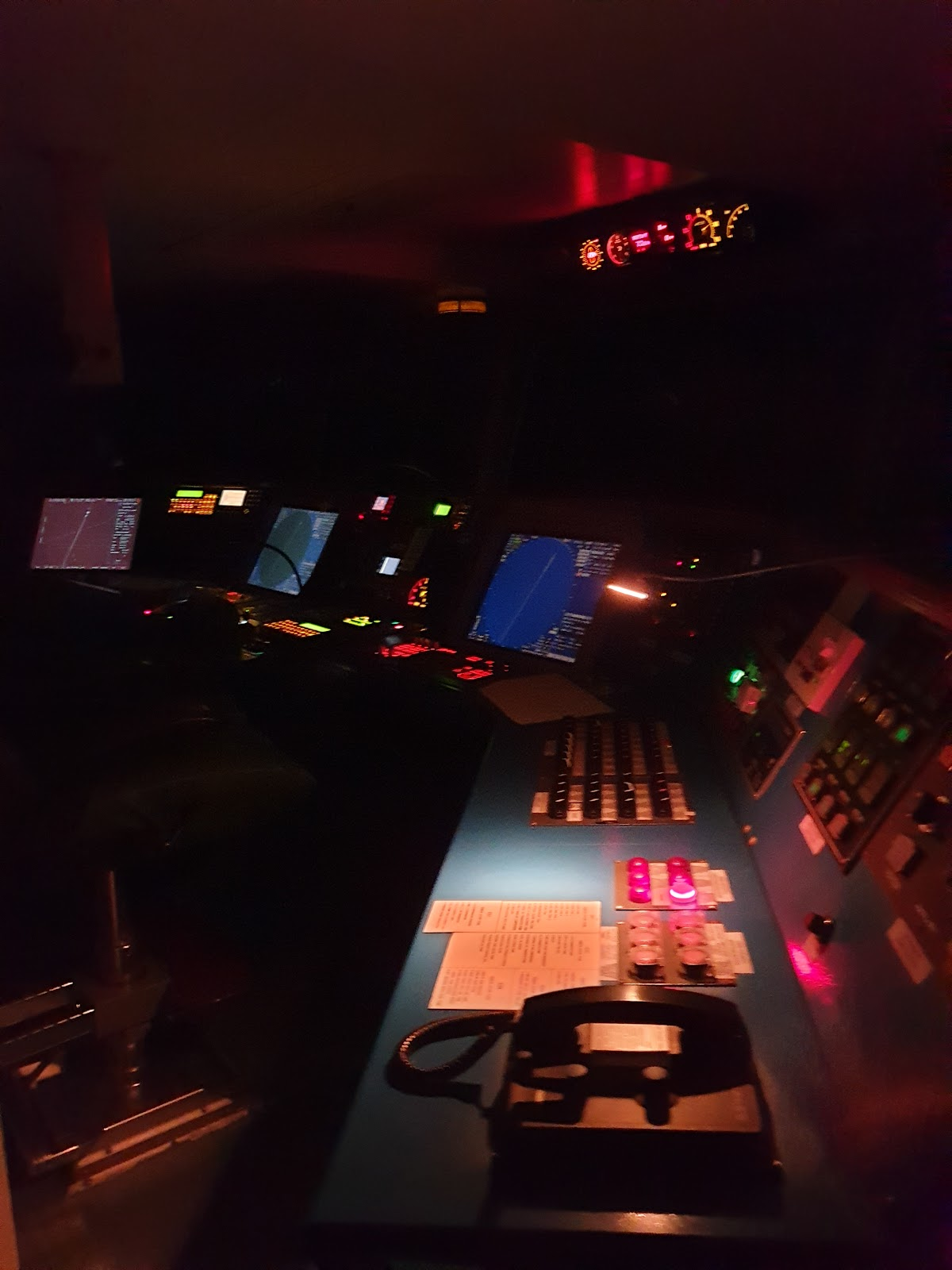 Container ship's control panels at night dimly lit