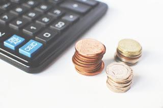 Gold-colored Coins Near Calculator