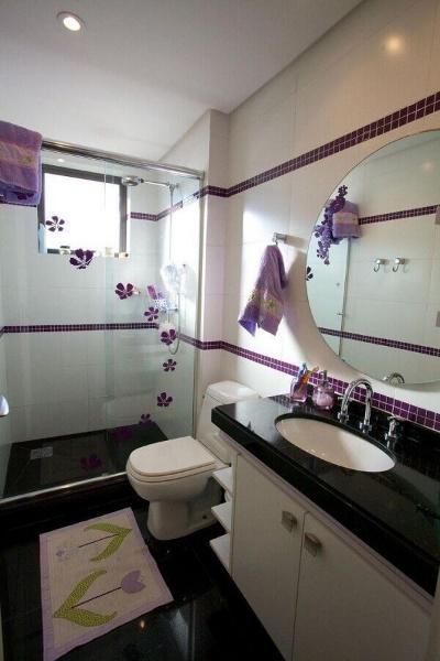 Banheiro com azulejo branco e pastilhas em linhas horizontais roxa, piso preto, box de vidro, vaso sanitário, gabinete branco com pia de mármore preta.