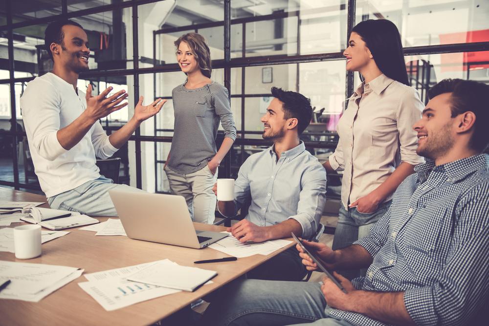 Várias pessoas conversando descontraídas em um escritório de trabalho.