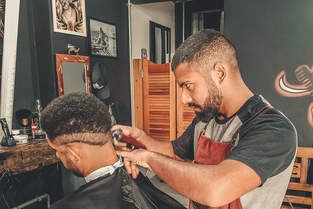 Man at barbershop getting his hair cut; prepare for your destination wedding