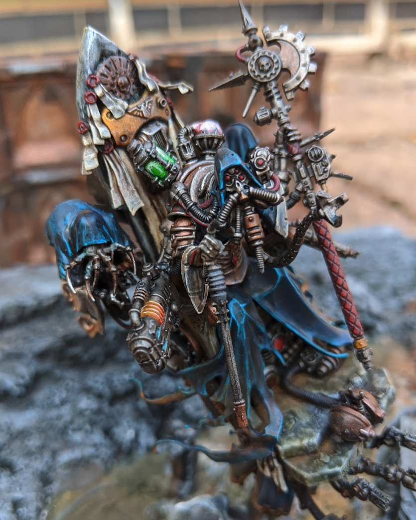 An Ad Mech Tech Priest mixed with a Nighthaunt Craven King model. A flying mechanical throne with attendants on either side clad in blue robes