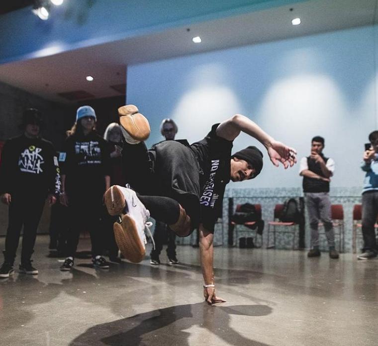 Grupo de pessoas sentadas em volta de uma rampa de skate  Descrição gerada automaticamente com confiança baixa