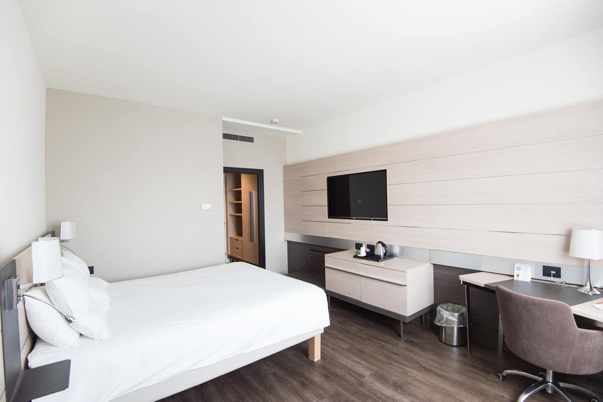 Una moderna camera di un hotel con letto, armadio e tv a schermo piatto