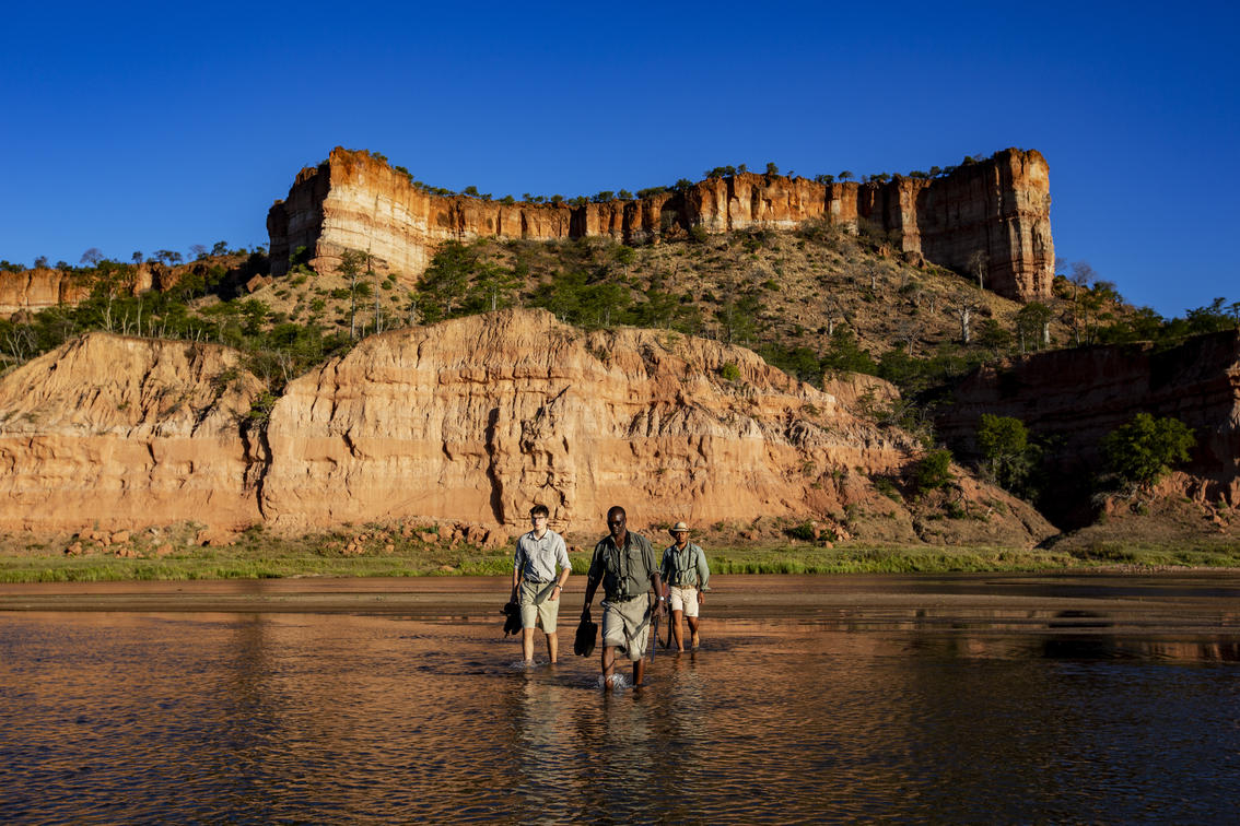 a guide walking with two men following him in font of cliffs in ghonarezhou zimbabwe