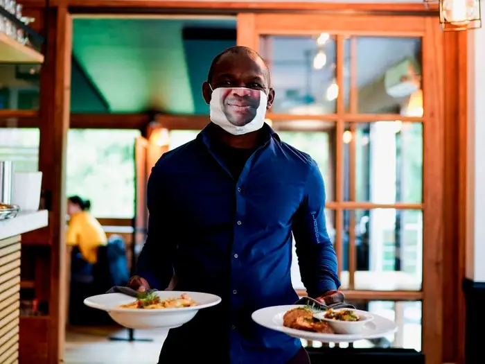 A restaurant waiter wearing a creative mask with a printed image of his face on it.