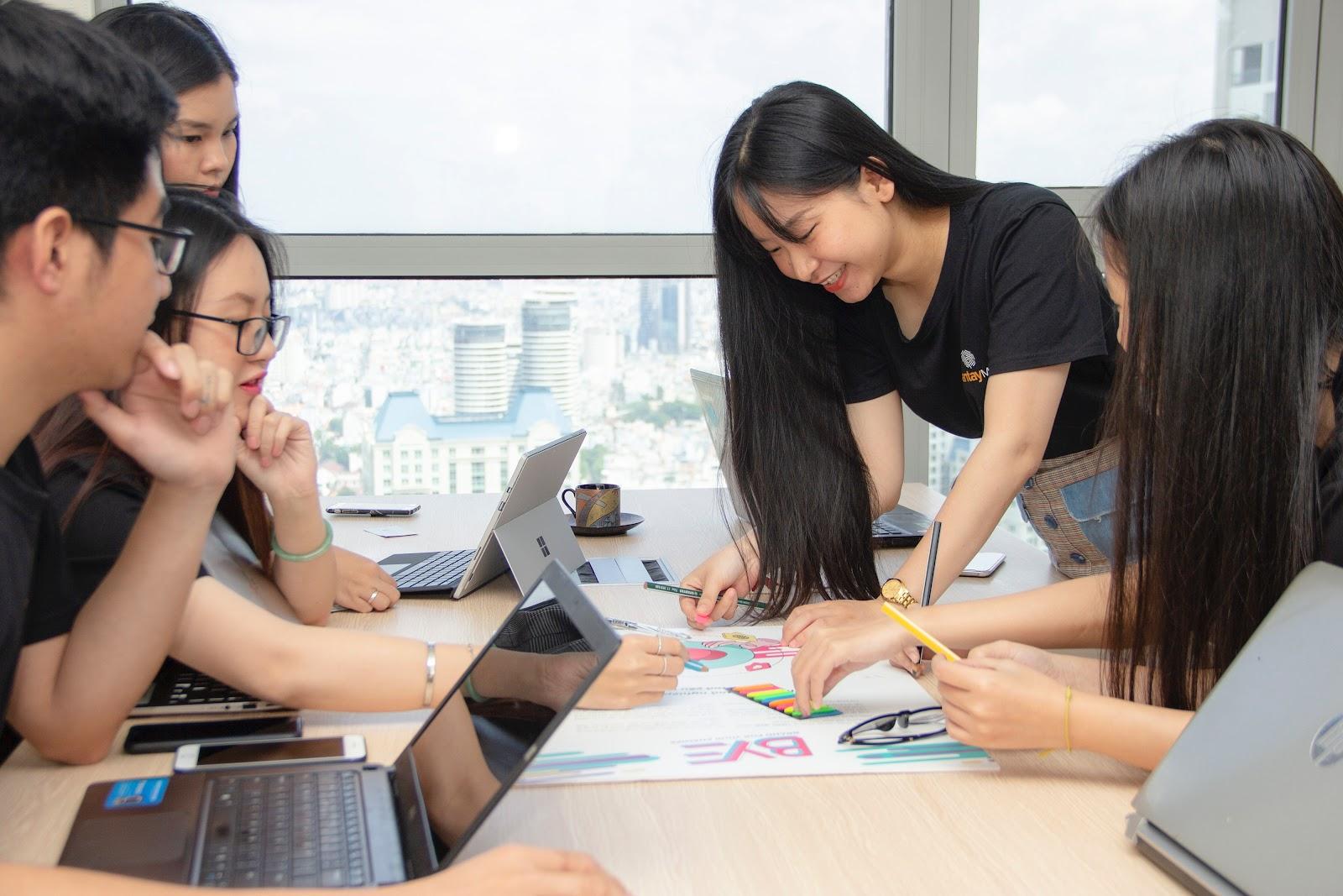 Grupo de trabalhadores realizando um workshop expondo ideias em uma cartolina