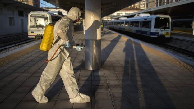 Медицинский работник распыляет антисептик на вокзале в Испании
