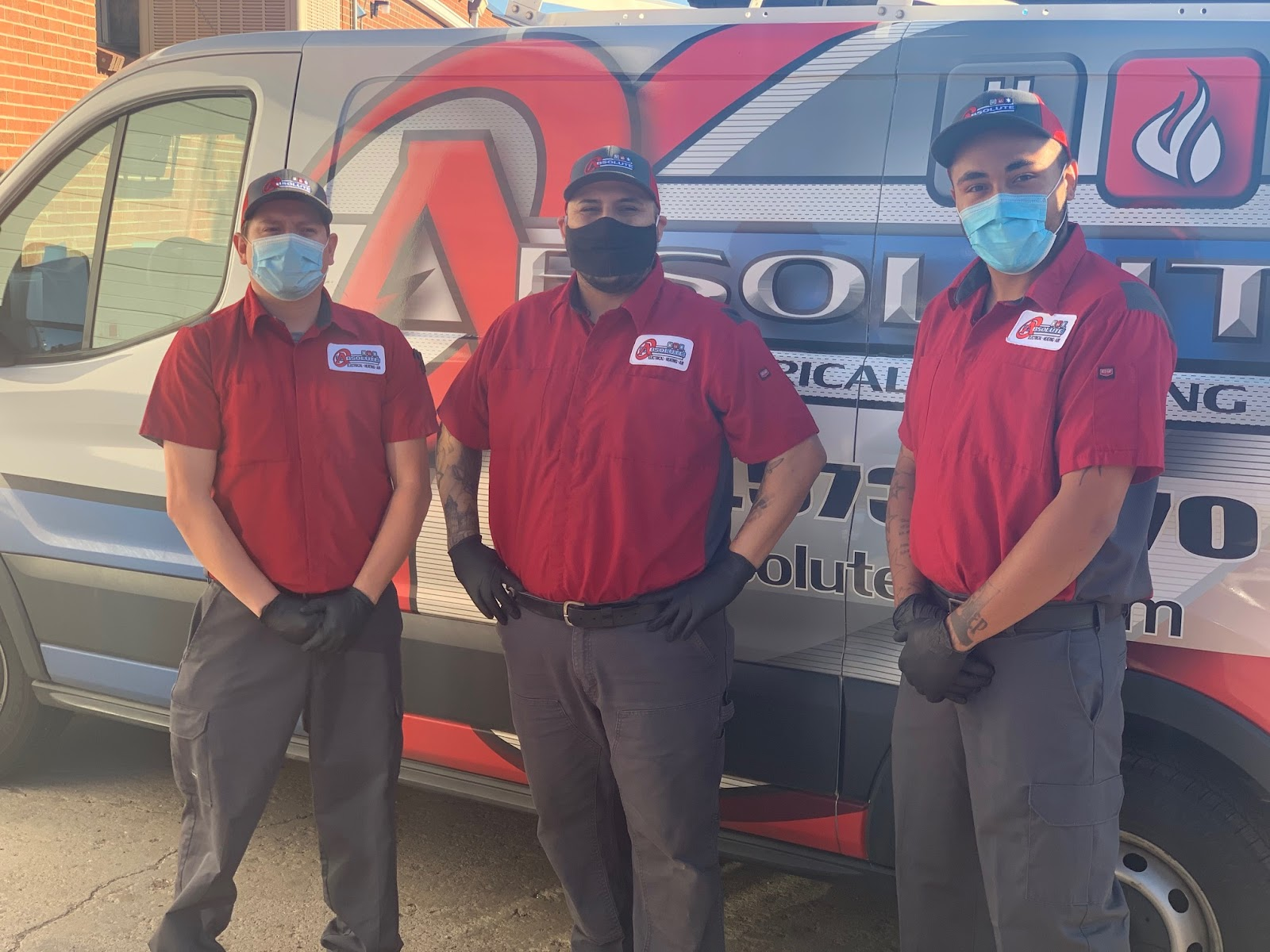 three electrical/HVAC techs in red shirts, grey pants, hats, protective gloves, and face masks smile in front of Absolute vehicle