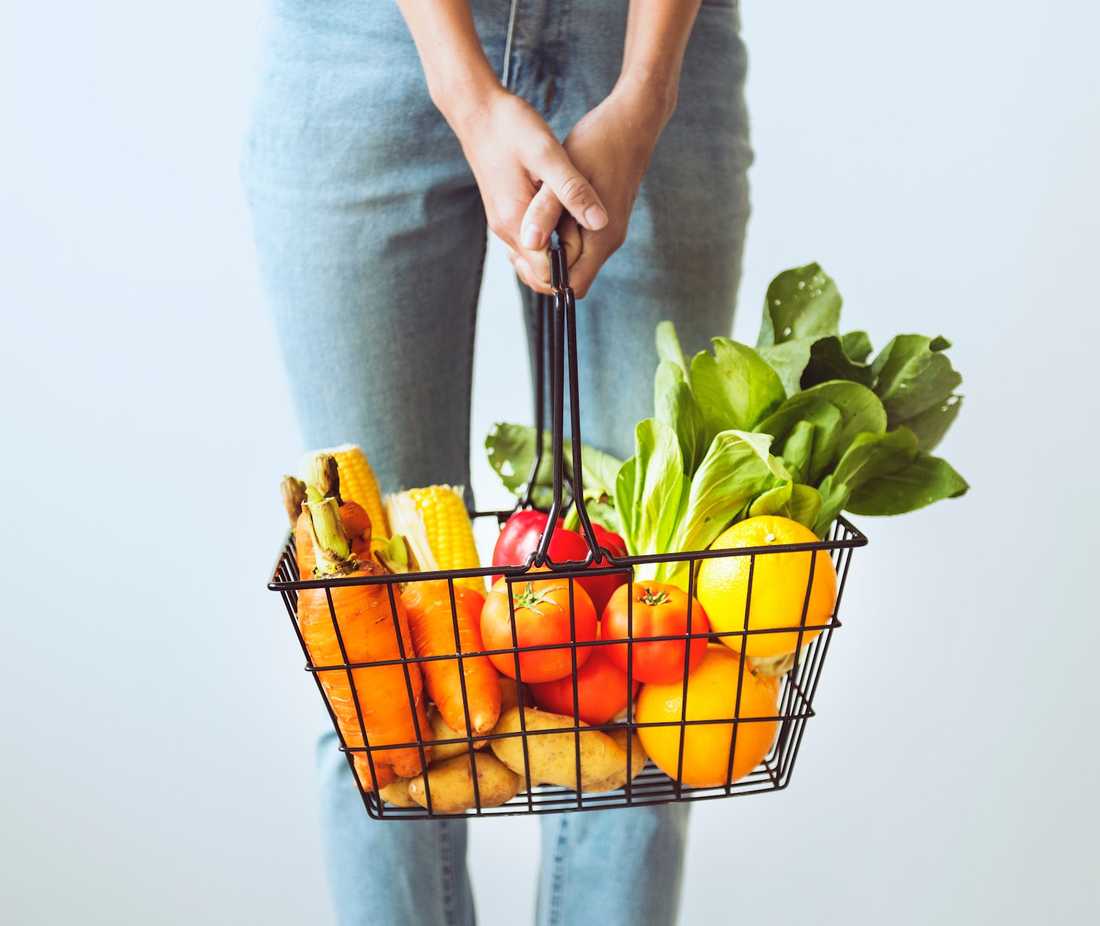 Woman holding basket full of groceries
