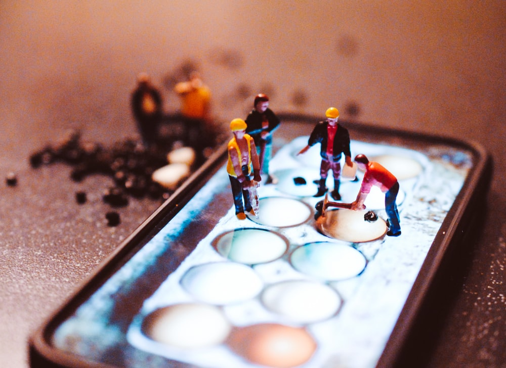 tiny model construction workers, working on a mobile phone screen