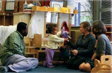 A toddler showing two caregivers a toy.