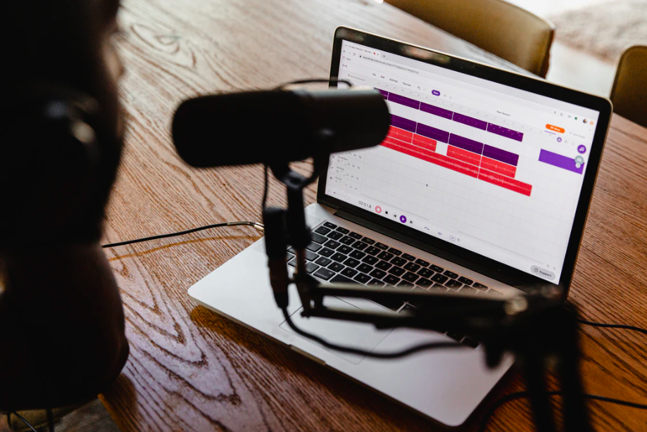 Designs.ai - Grow Your Podcast Audience With These 5 Simple Steps, podcaster planning and recording