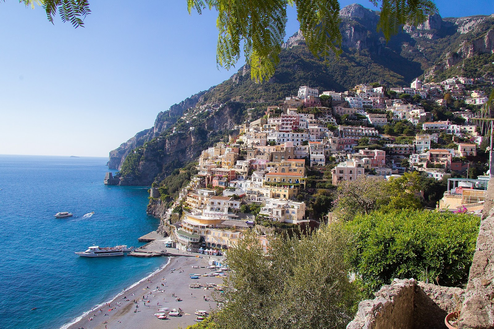 amalfi coastal village beach tourists and ships traditional italian village on seaside cliff hills in background