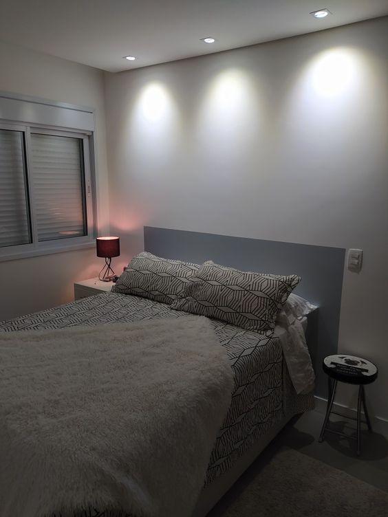 Quarto minimalista com cabeceira cinza em forma de pintura na parede, cama de casal e banquetinha decorativa.