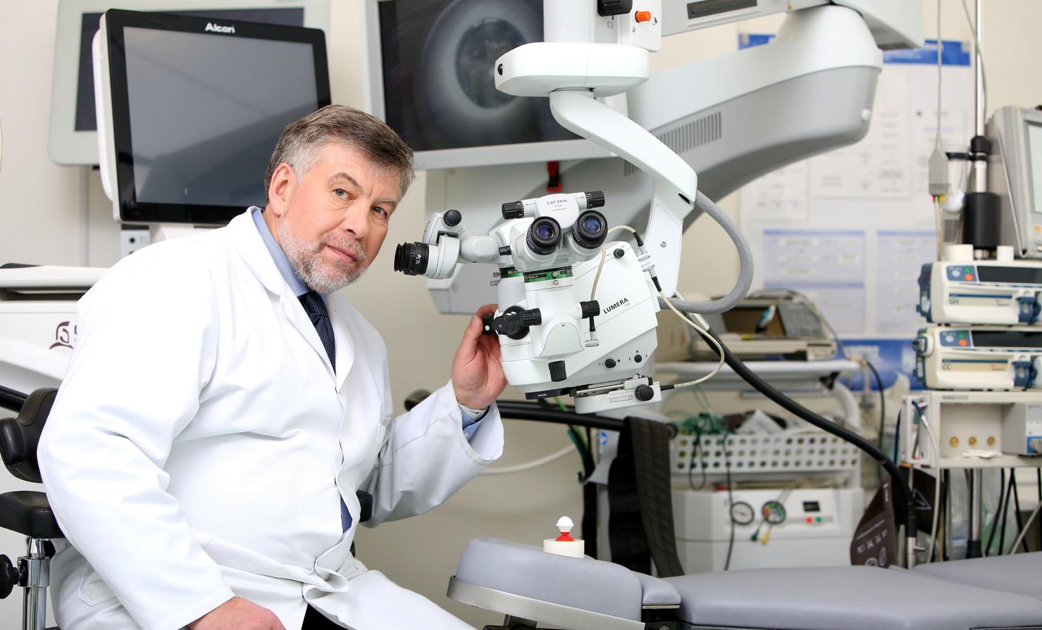A person on a microscope Description automatically generated