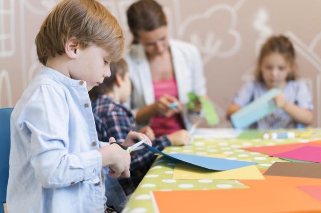 Foto da vista horizontal de 3 crianças e uma mulher adulta professora, realizando uma atividade de recorte em folhas de papel, visando ilustrar a cultura maker, já que cada criança está realizando sua atividade de maneira independente.