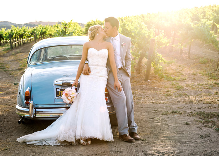 wedding couple leaning on car in an orchard