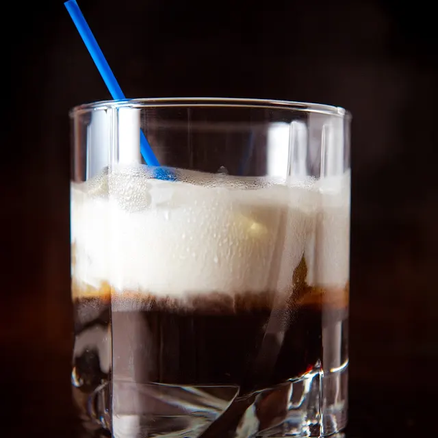 A Dirty White Russian cocktail in highball glass with a blue straw