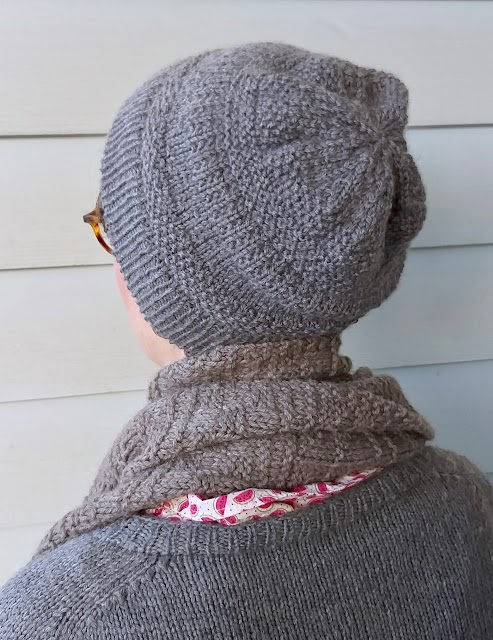 Siobhan stands in front of a weatherboard wall, wearing a grey handknit textured hat, similar style scarf, and plain grey handknit jumper. She is turned to the back to showcase the square hat peak created by the decreases.