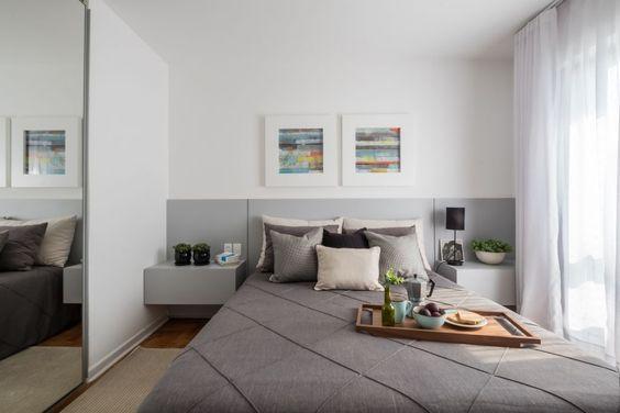 Quarto em tom branco e cinza, com cabeceira e criado mudo de MDF cinza, piso de madeira e parede branca.
