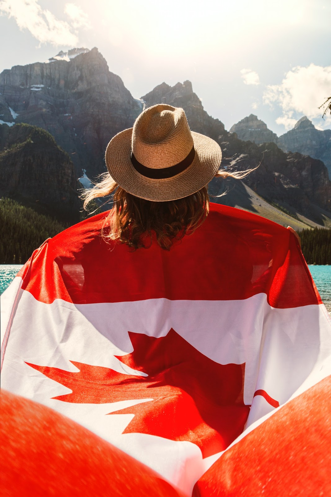 lady holding canada flag overlooking the mountains