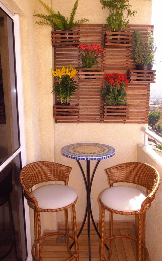 Varanda com jardim vertical e banqueta redonda com duas cadeiras amadeiradas.