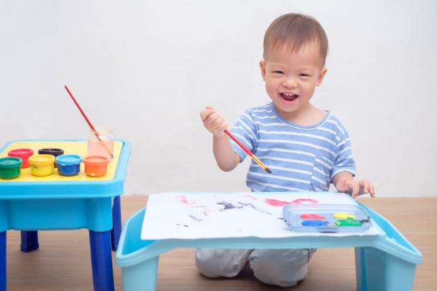 Imagem de um menino ajoelhado no chão, segurando um pincel com uma mesa feita para seu tamanho com um papel sulfite em cima e, também, com uma tampa com diversas amostras de tinta. Ele está com uma feição sorridente e animada, que ilustra a importância das competências socioemocionais.