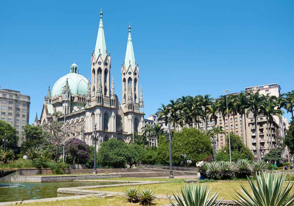 Vista lateral da Catedral da Sé, durante o dia, rodeada de árvores e prédios.