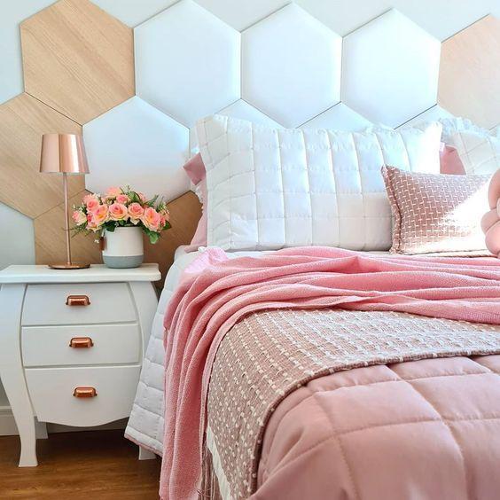 Quarto com cama de casal com cabeceira estofada em formatos hexagonal, amadeirado, branco e rosa, criado mudo branco com abajur e piso de madeira