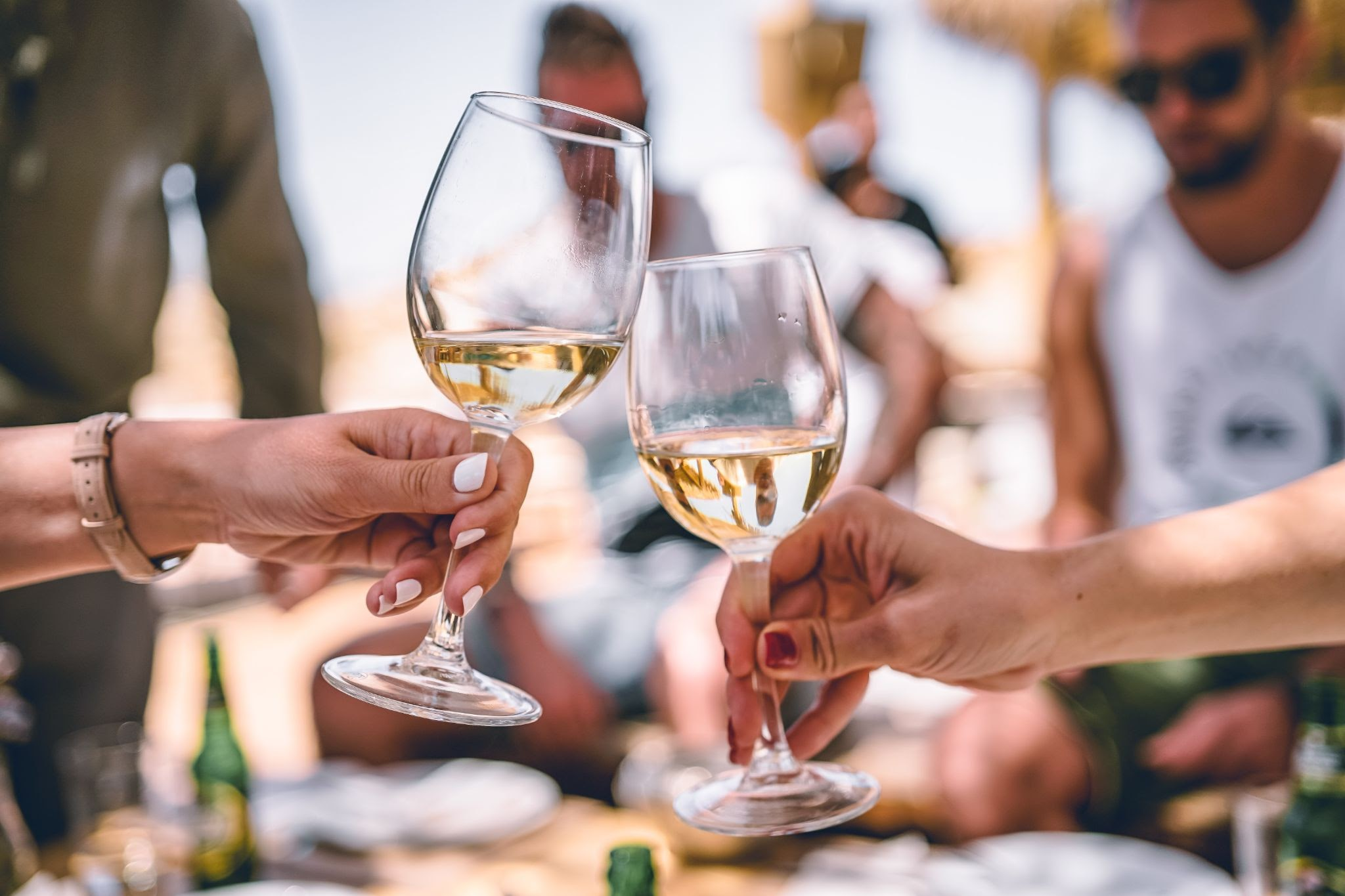 two hands cheers'ing white wine in glasses on a local kelowna wine tour